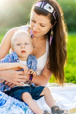 Young Mother with her son in a park, Child has Cerebral palsy