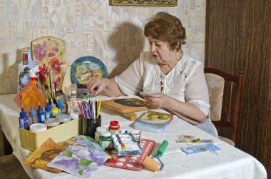 Happy elderly woman - artist makes decoupage