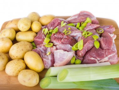 Meat pieces and potatoes on a chopping board