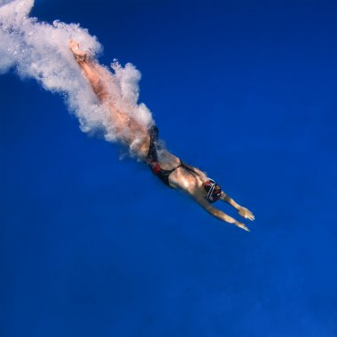 Professional female swimmer after jumping with air bubbles trail in blue water