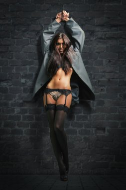 Attractive brunette in sexy lingerie and men's jacket posing