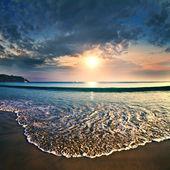 Fotografie Summer sea design template. Beautiful sunset on tropical beach with shorebreak and sunlight on horizon