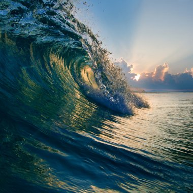 Summer design template. Beautiful sunset with surf and sunlight through breaking wave