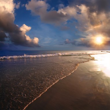 Tropical design postcard. Beautiful sunset on sand beach with sea foam and cloudy sky