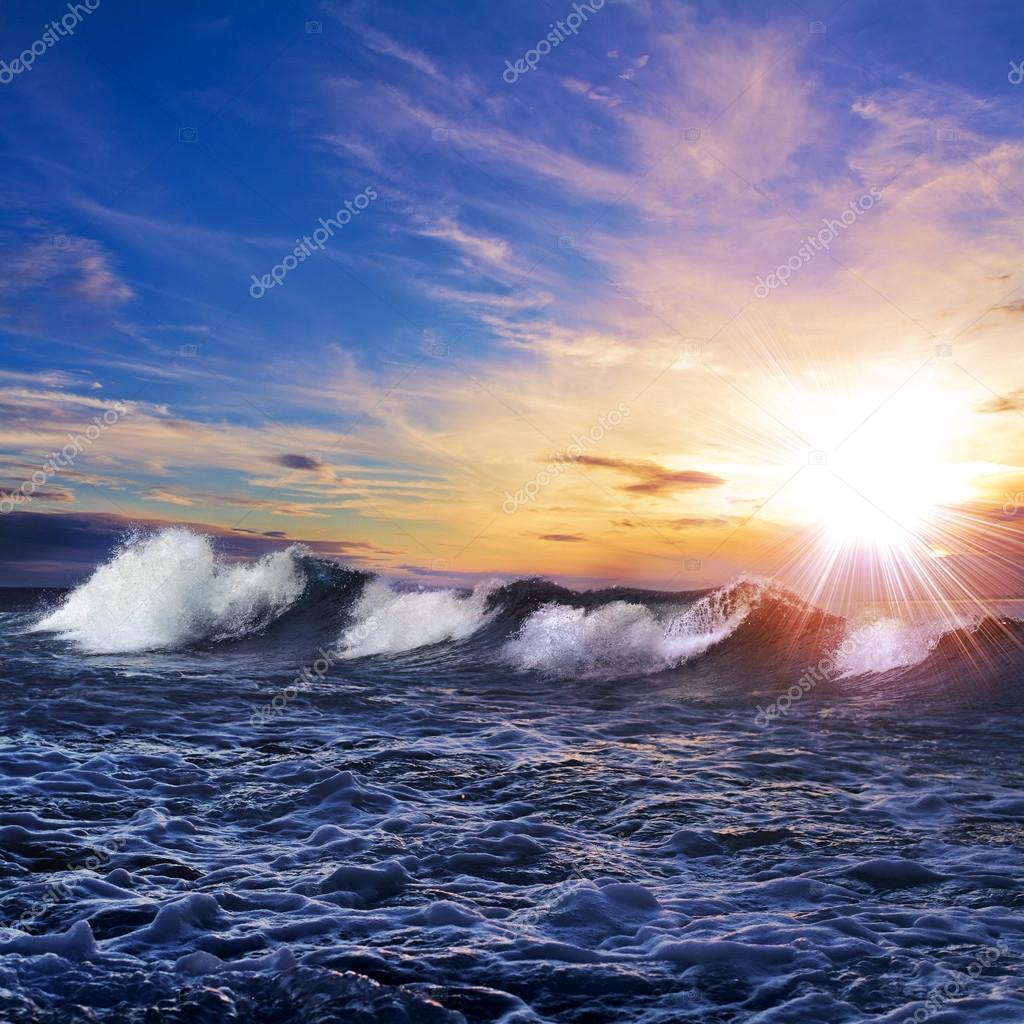 Beautiful background. Seaview with breaking waves pink clouds at the sunset time