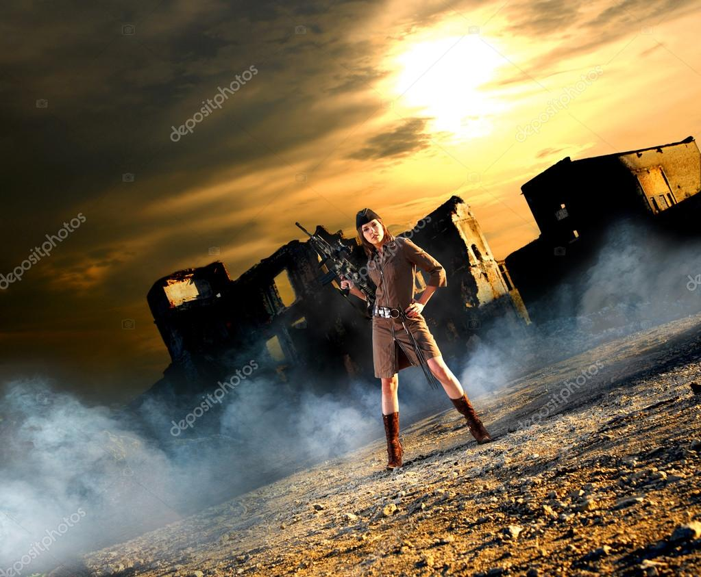 Young and sexy woman with the machine gun in apocalyptic landscape