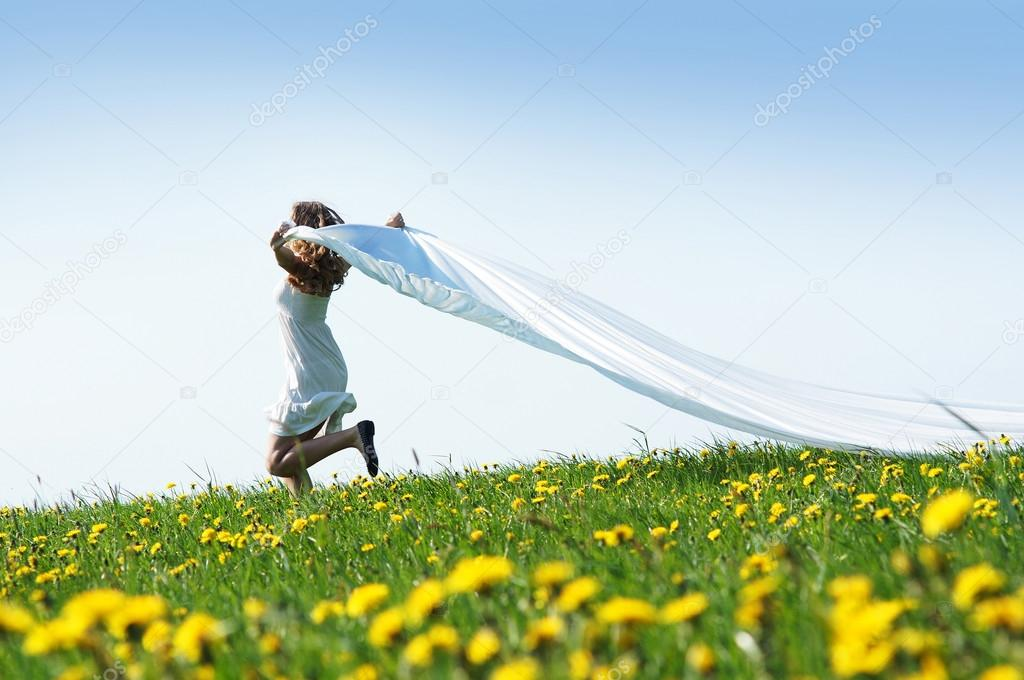 Young beautiful girl running in a meadow