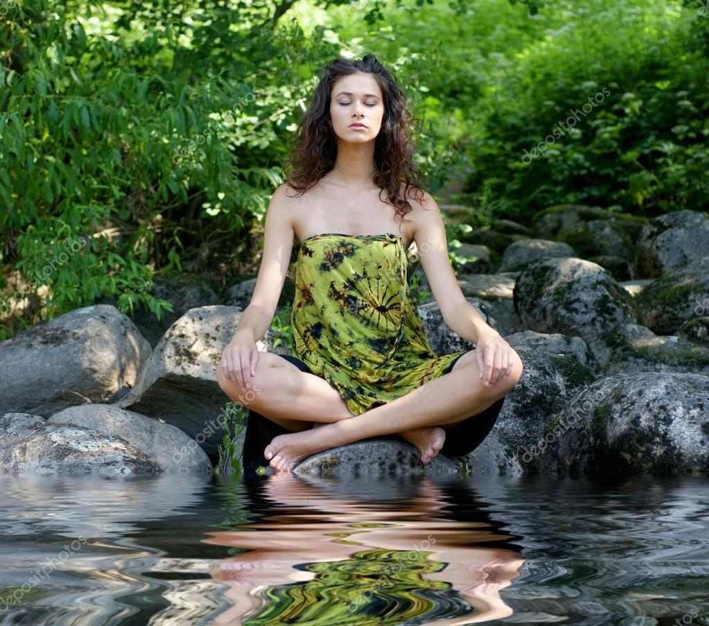 Young healthy woman meditating in the forest