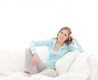 Young, attractive, happy woman sitting in the bed