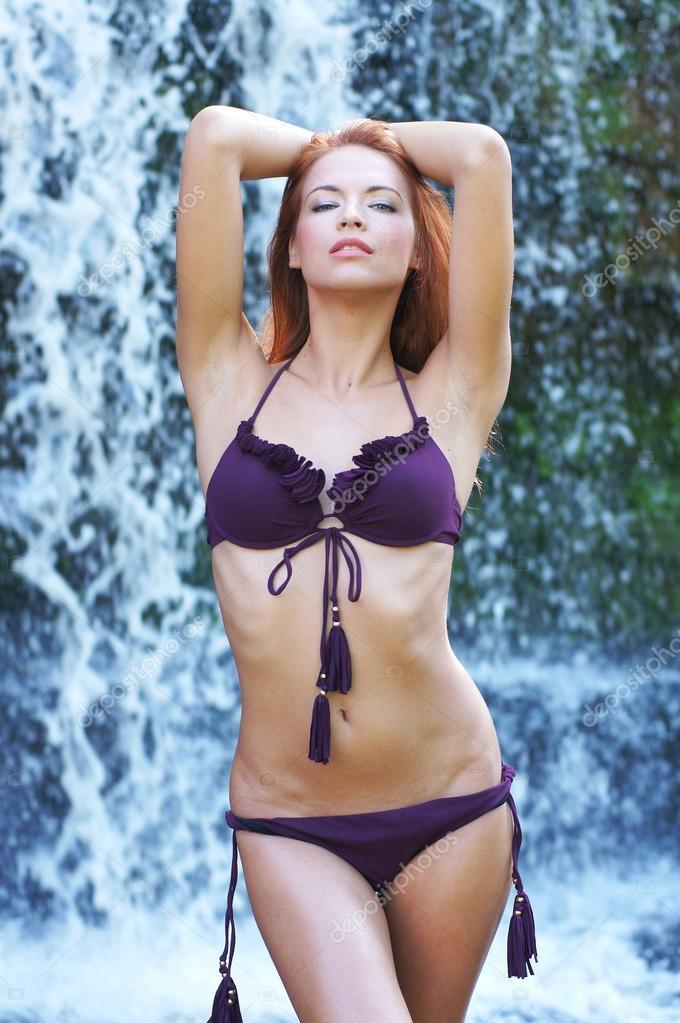 Young and beautiful girl in bikini taking bath in a waterfall