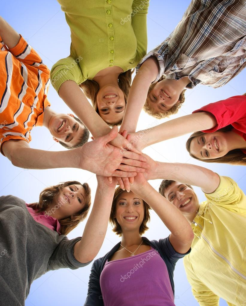 Group of smiling teenagers staying together and looking at camer