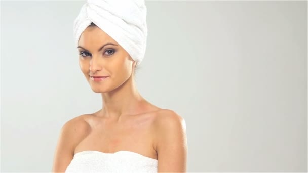 Portrait of young beautiful woman with the towel on her head in spa