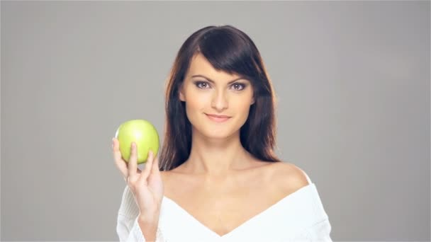 A young and happy woman sharing a fresh green apple