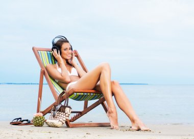 sexy woman listening to the music on the beach