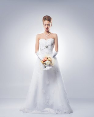 Young and beautiful bride standing with the flower bouquet