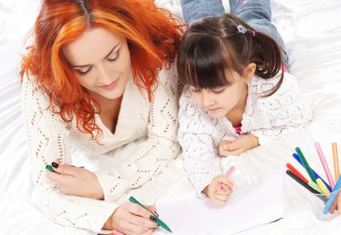 A happy mother and a little daughter drawing with markers