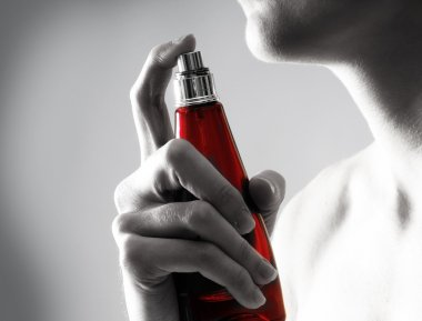 Young attractive woman with the bottle of perfume
