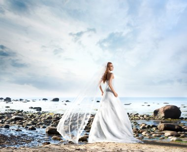 Young, beautiful and lonely bride dreaming on the beach