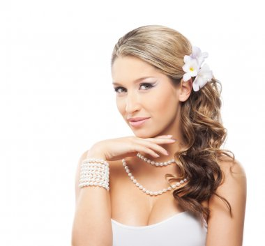 Beautiful woman with a pearl jewelry and a flower in her hair