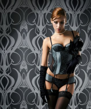 A young redhead woman posing in luxurious lingerie