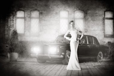 A young bride in a white dress posing next to a car