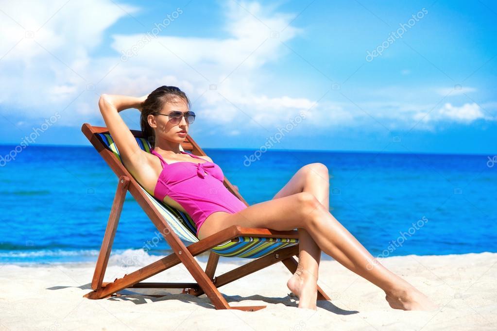 Девушка на шезлонге лежит картинка на пляже боком