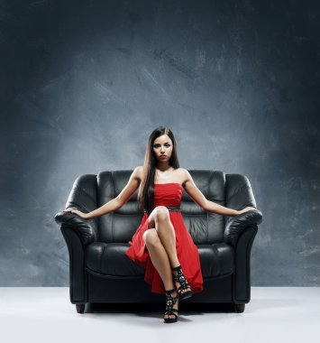 Woman in red dress sitting on the black leather sofa