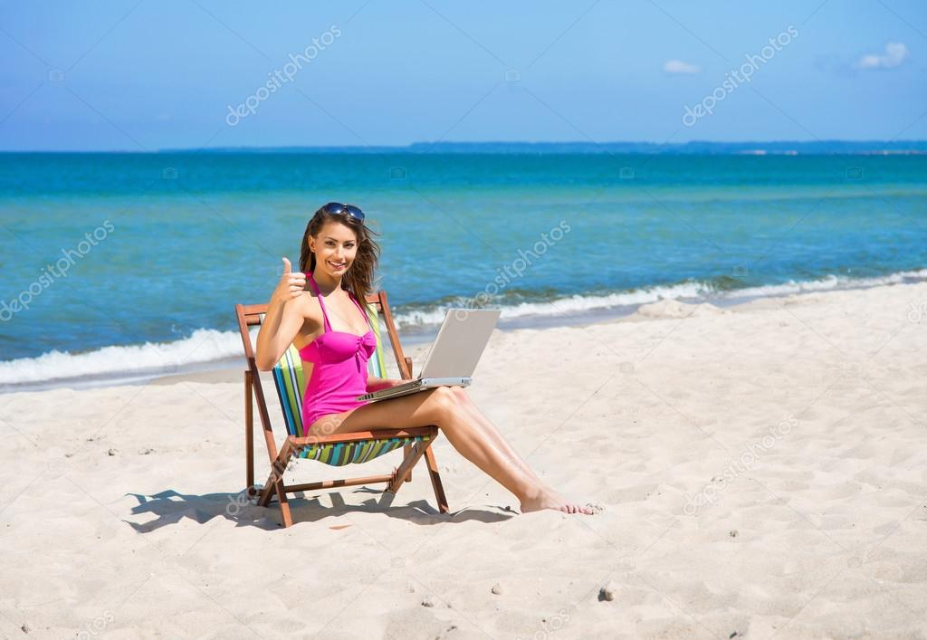 A young woman in a swimsuit relaxing on the beach