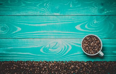 beautiful white coffee cup with coffee beans on turquoise wooden Toned in warm colors