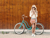 Young sexy blonde girl with long hair with brown vintage bag in sunglasses standing near vintage green bicycle and holding a cup of coffee, have fun and good mood looking in camera and smiling, warm,