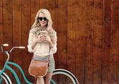 Mladá sexy blondýna s dlouhými vlasy s vintage umaštěný v brýle, stojící poblíž vintage zelené kolo a drží šálek kávy, mají zábavu a dobrou náladu při pohledu v kameře a usmívá se, teplé