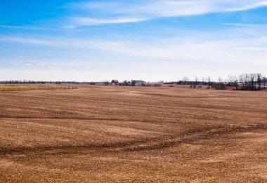Empty brown farm fields on sky.