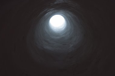 Dark tunnel leading into light opening.