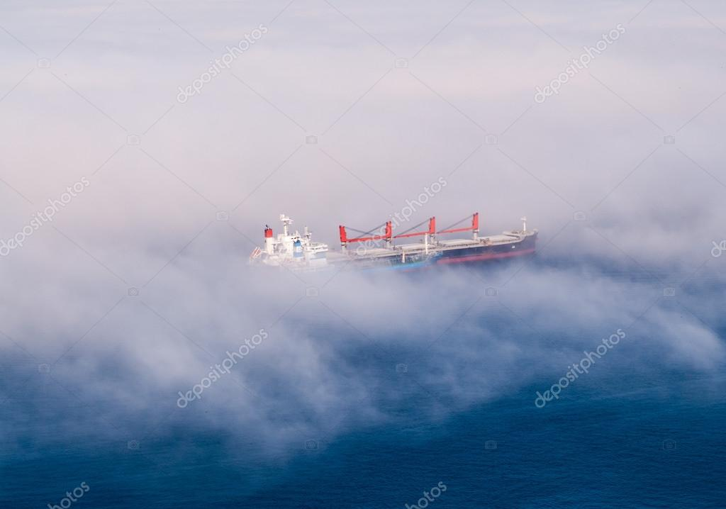 Large cargo ships in partial fog.