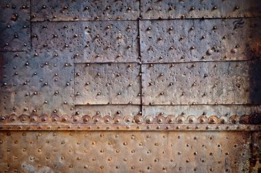 Old door rusty metal cover with rivets