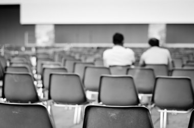 Men sitting on empty chairs
