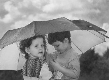 Little girl and boy hiding under an umbrella from the rain, blac