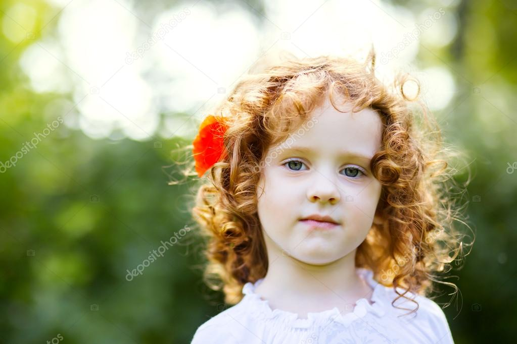 curly little girl with a flower in her hair
