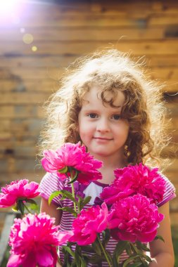 Child smelling bouquet of peonies, sun backlighting. Toning phot
