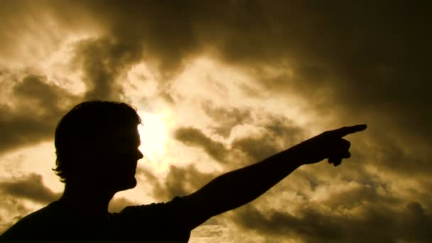 Person silhouetted raises arm and points finger in a forward direction