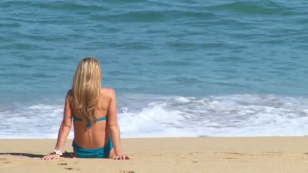 Long haired blonde woman enjoys a perfect day at the beach in Cabo San Lucas, Mexico by resort.