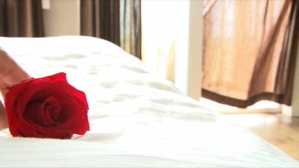 Red rose lays on white linen bed at resort.