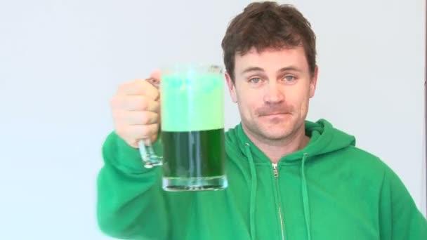 šťastný muž, oblečený v zelených nápojů od hrnek zelený kapalinou