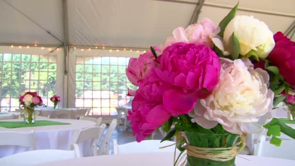 Tented wedding setting viewing large floral centerpieces .