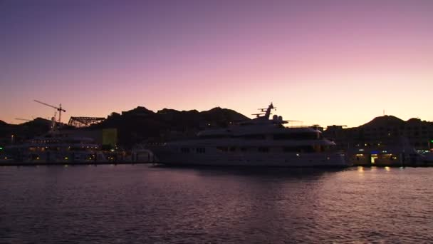 Cabo San Lucas, Mexico boating into downtown harbor with pelicans flying and luxury yachts.