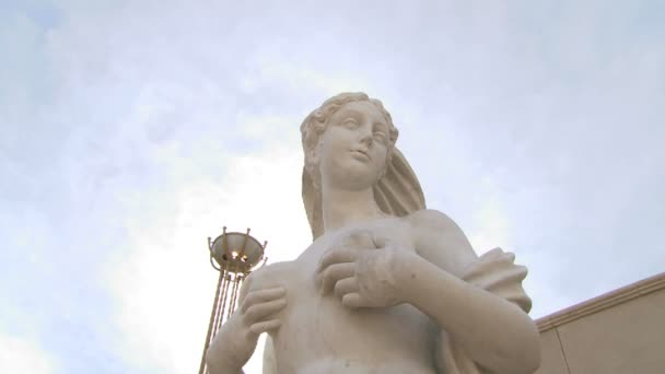 statue of a naked woman on a background of blue sky