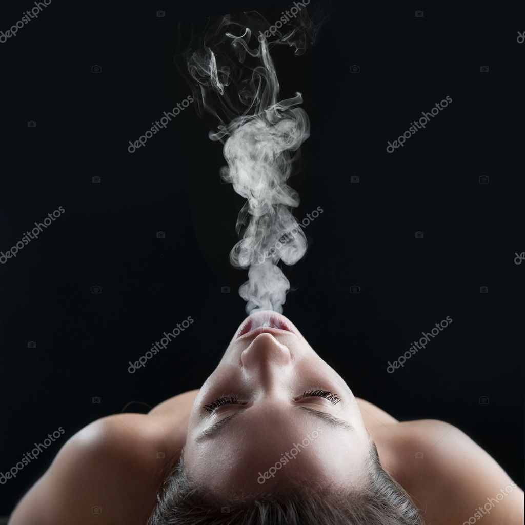 Woman blowing smoke against dark background. Studio fashion phot