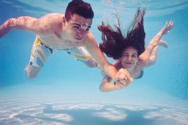 Underwater couple holding hands in swimming pool.