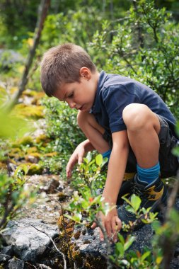 Portrait of six year old boy playing outdoors in the mountains.
