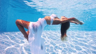 Underwater woman fashion portrait with white dress in swimming pool